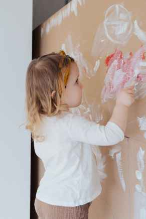 girl in white long sleeve shirt holding paint brush